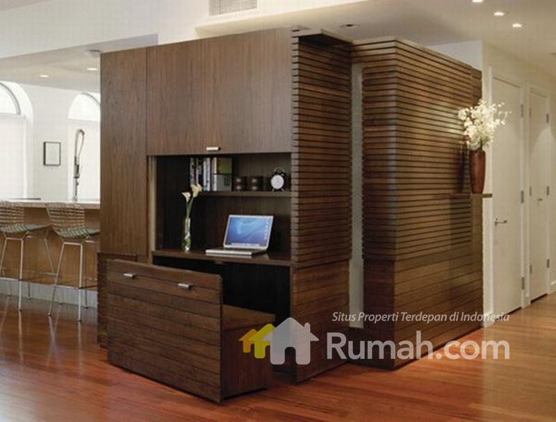 Desain ruang kerja yang menyatu dengan lemari buku dan pakaian, seakan tersembunyi di sudut ruang.