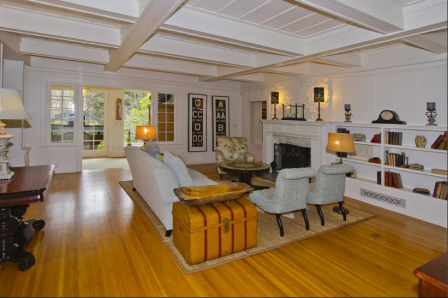 Suasana ruang keluarga terasa nyaman dan akrab berkat nuansa putih berpadu lantai kayu yang dihadirkan. Peti harta karun berwarna coklat yang dimanfaatkan sebagai meja, menjadi keunikan tersendiri bagi dekorasi ruangan.