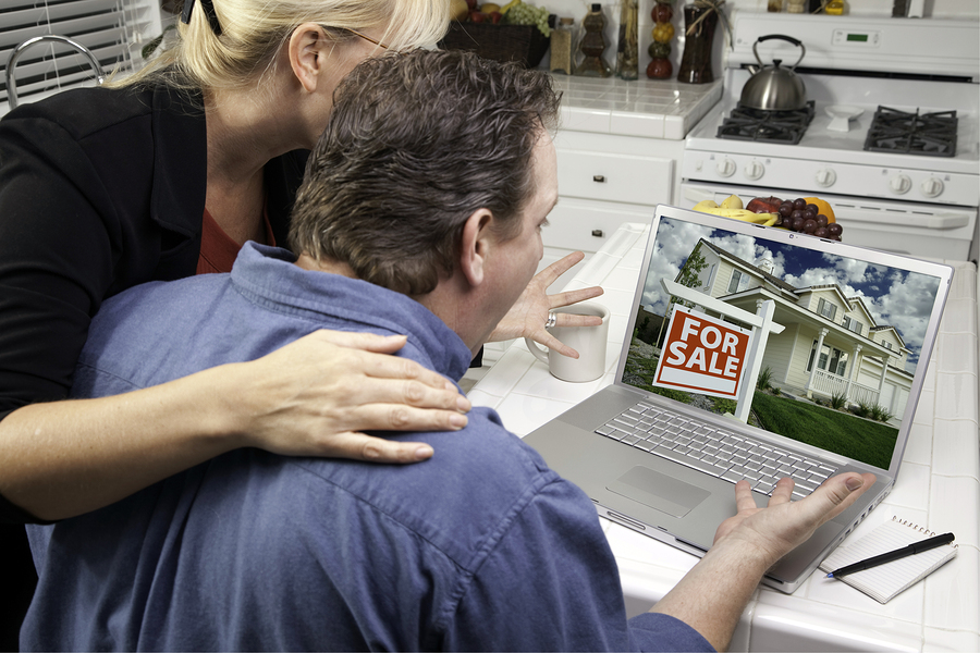 Couple In Kitchen Using Laptop to Research Real Estate. Screen can be easily used for your own message or picture. Picture on screen is my copyright as well.