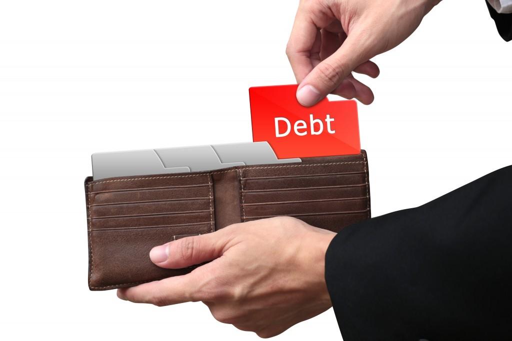 Businessman hands pulling red folder DEBT concept on brown walle