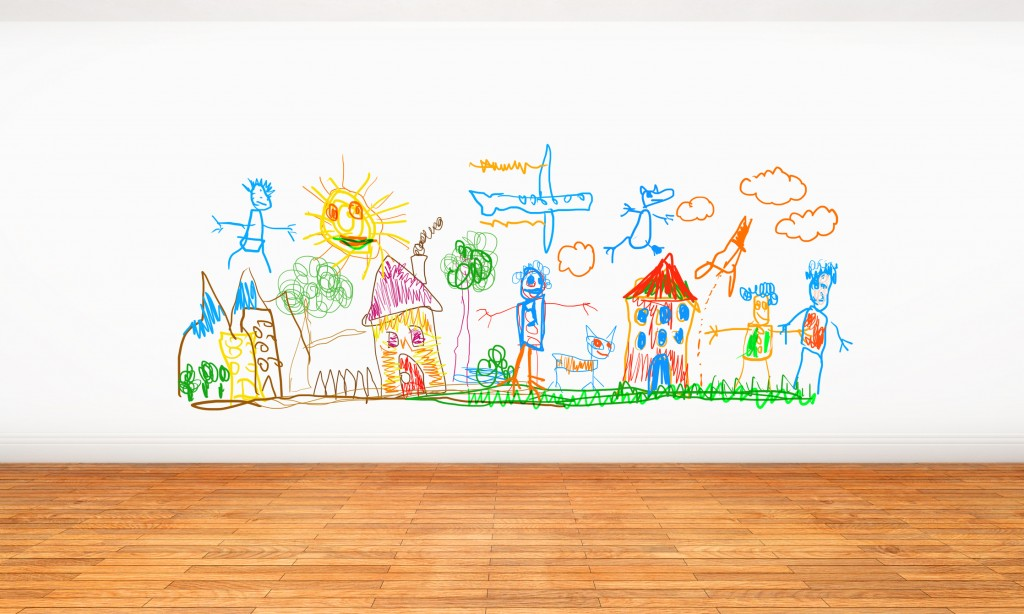White wall full of childhood scribbles, colorful doodles and crayon drawings painted by children in their home. Young creativity and fun at home. White wall with brown hardwood parquet.