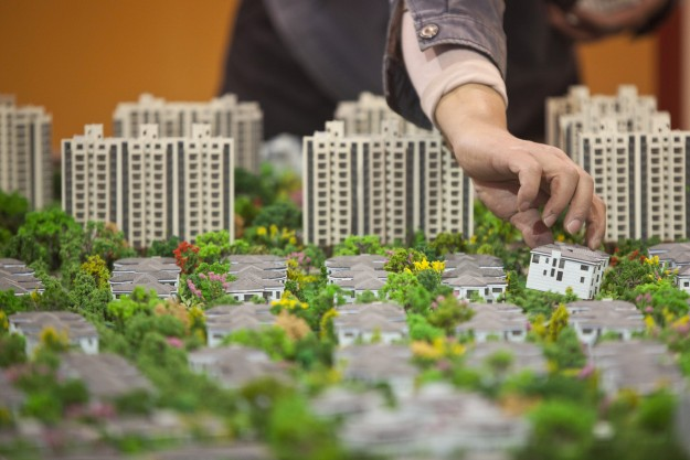 A worker installs models in preparation for a real estate exhibition in Shanghai
