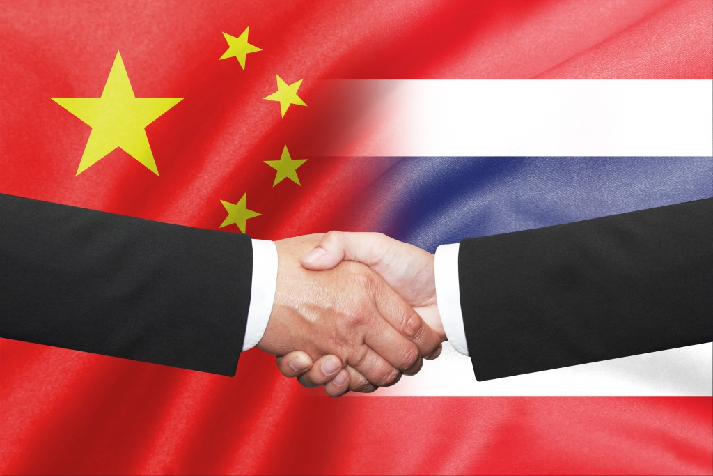 Isolated two business man shakehand over thai and china flag