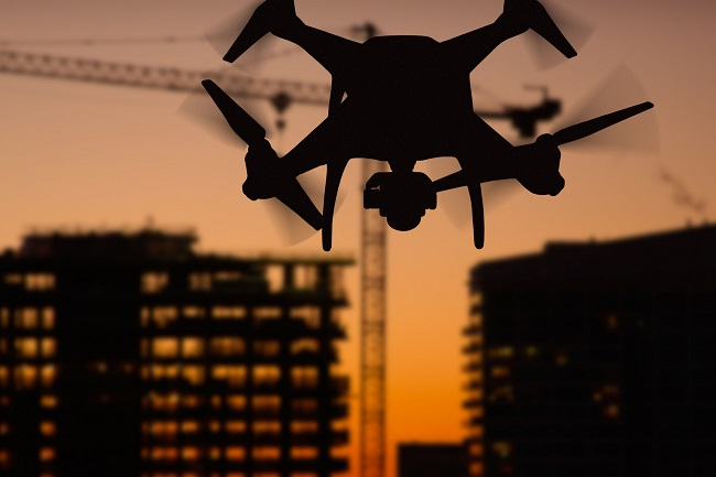 78735086 - silhouette of unmanned aircraft system (uav) quadcopter drone in the air over buildings under construction.