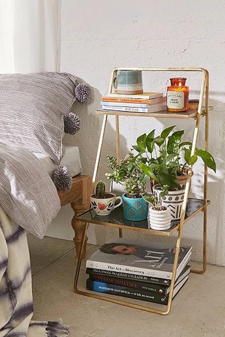 Biarkan tanaman tetap di rak bagian tengah untuk menyegarkan kamar. Biasanya bentuk rak ini akan ramping sehingga tidak memakan banyak ruang.
