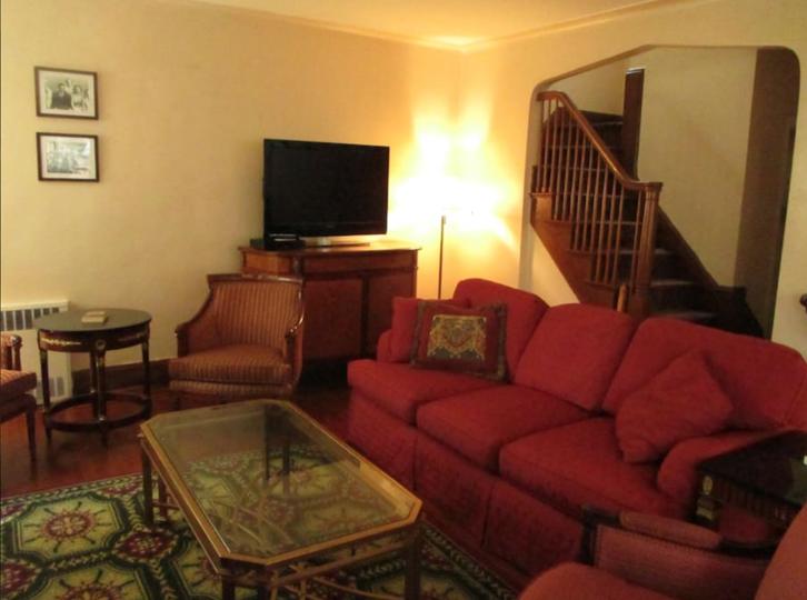Anda dapat melihat ruang keluarga bernuansa klasik dengan sofa merah besar yang elegan.