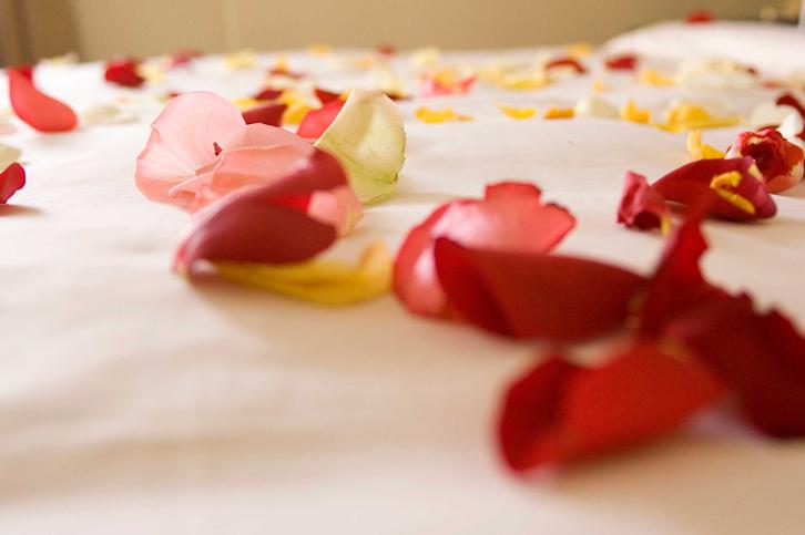 Warna pink bisa Anda gunakan pada selimut, lingerie yang dipakai, bantal, atau helai bunga mawar yang sengaja di sebar di atas ranjang.