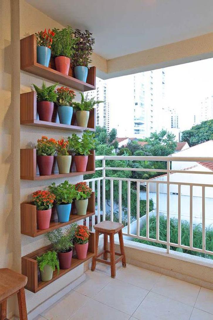 Pasanglah rak-rak kayu di dinding lalu letakkan pot-pot tanaman dengan rapi di rak tersebut.