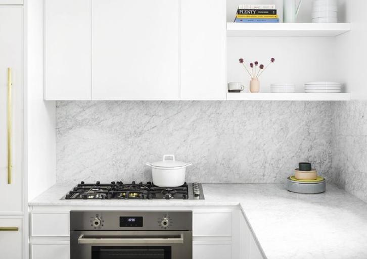 Area dapur pun didesain dengan dominasi warna putih dilengkapi kitchen set, rak, dan lemari yang berpadu kontras dengan lantai gelap.