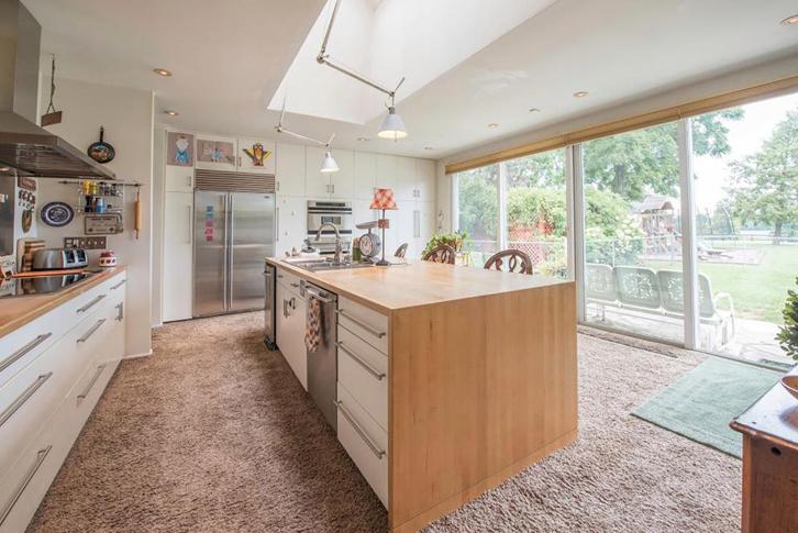 Warna putih yang mendominasi ruang berpadu apik dengan aksen kayu pada furnitur dan permukaan meja dapur.