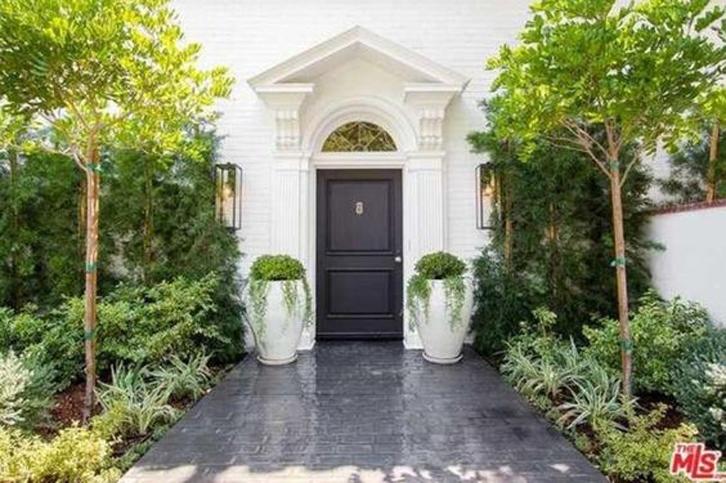 Agar tampilan teras berbeda, cat pintu rumah dengan warna gelap