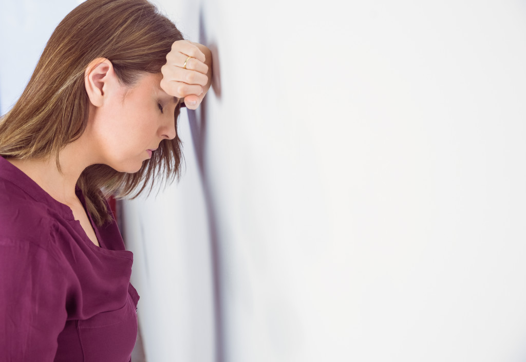 Depressed woman leaning her head against a wall on white background