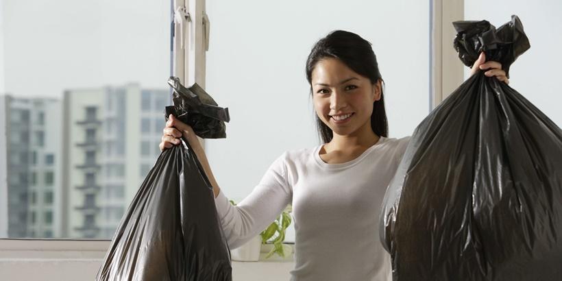 Asian girl holding trash bags crop