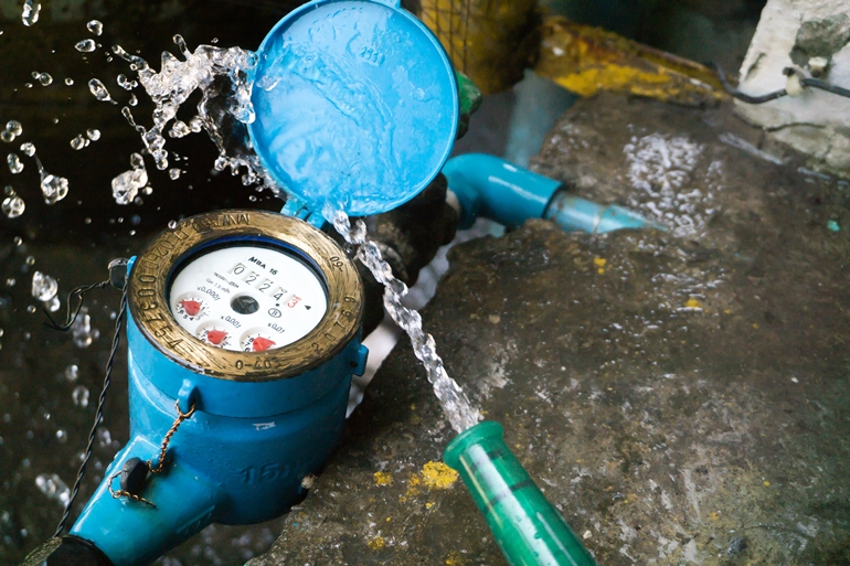 Close up water meter blue color in thailand. And a hose with flo
