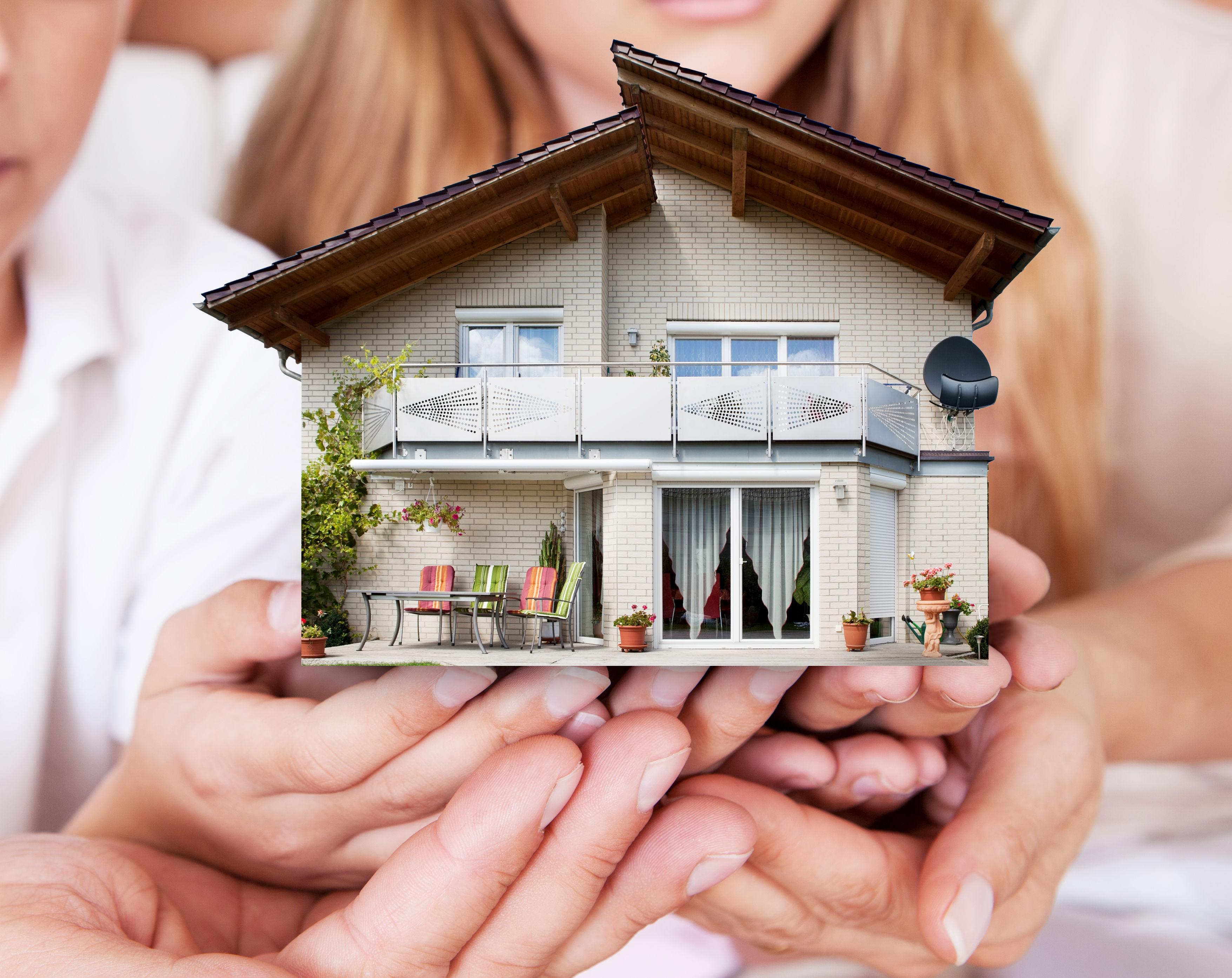 close-up of family holding the house model together