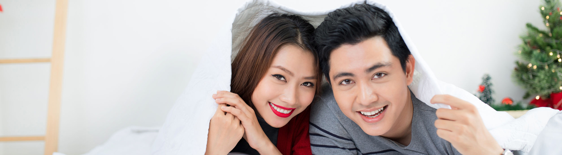 70897896 - christmas. asian couple at home celebrating new year.