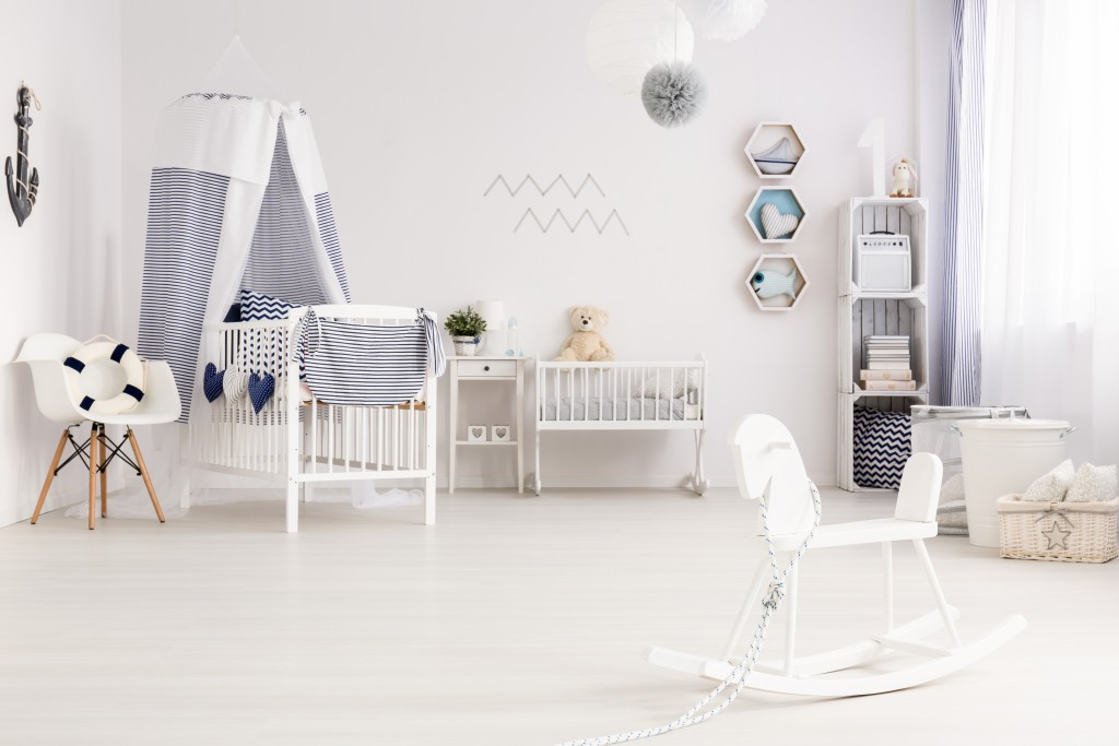 Airy baby room agganged in white and navy blue, with marine decorations