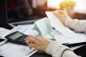 101540991 - close up of woman hand calculating her monthly expenses with calculator.  debt.