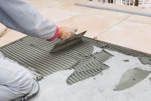 36113767 - home improvement, renovation - handyman laying tile, trowel with mortar