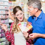 Couple choosing color of paint in hardware store