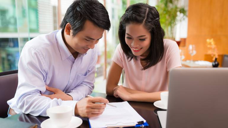 Two individuals looking through a tenancy agreement in a cafe - PropertyGuru