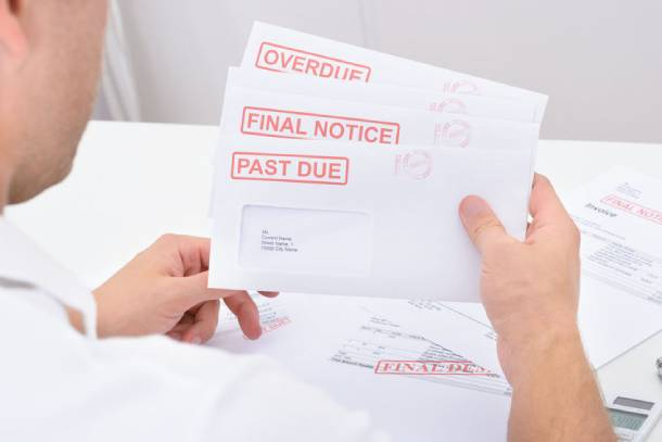 A man holding on to a few late payment notices