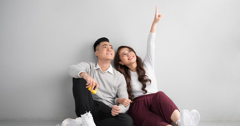 Young asian adult couple sitting on flor planning new home desig