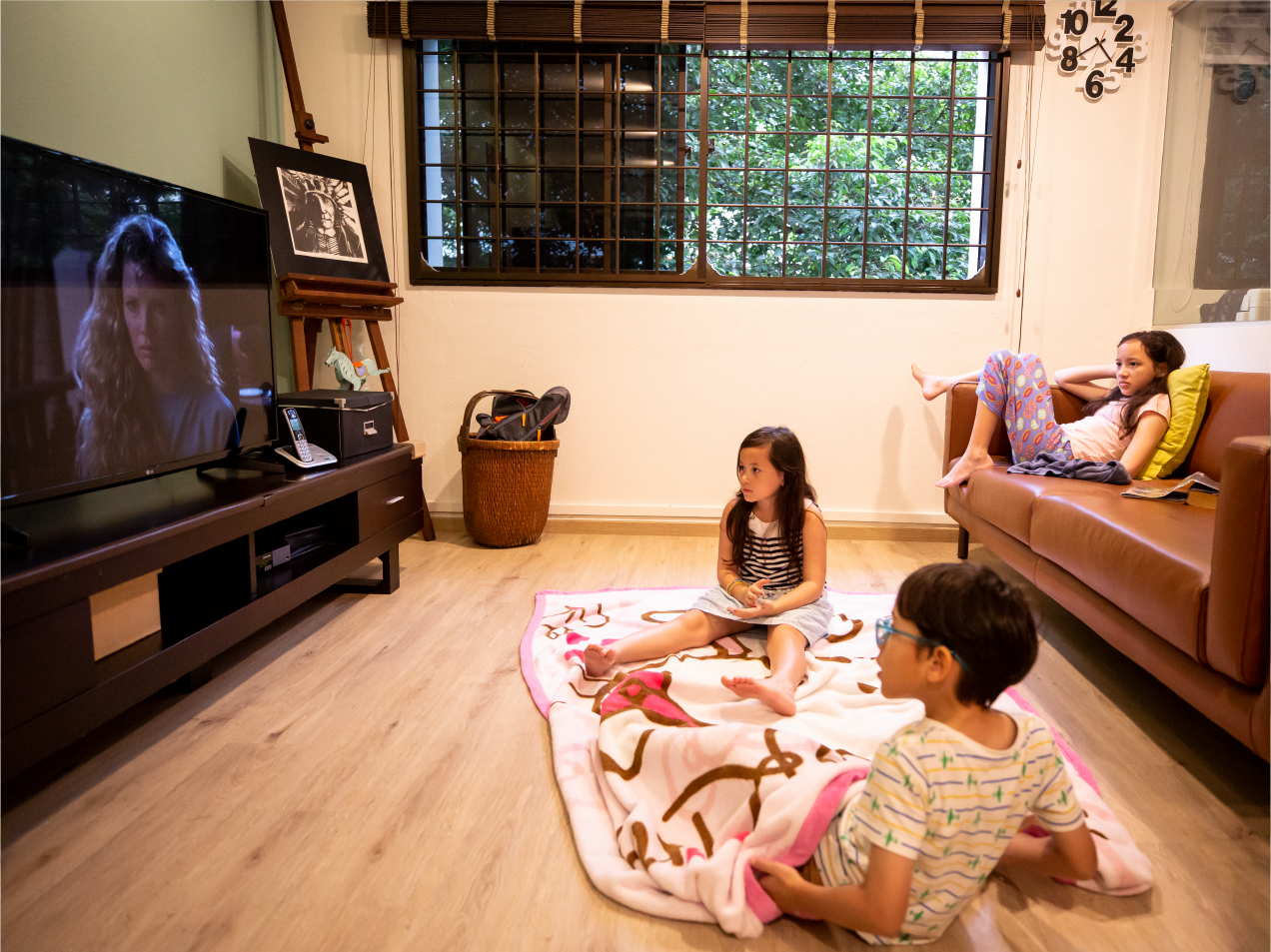 David's children watching TV in the living room of their HDB flat in Bishan