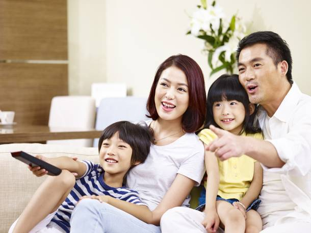 A young Singaporean family watching television together
