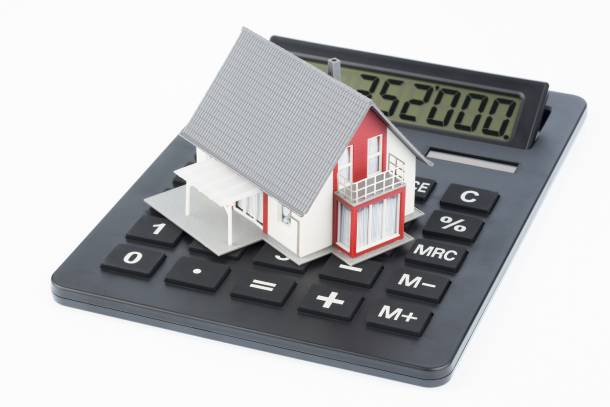 A small model of a bungalow atop a calculator