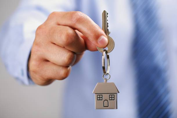 An individual holding a house key after ROF Scheme
