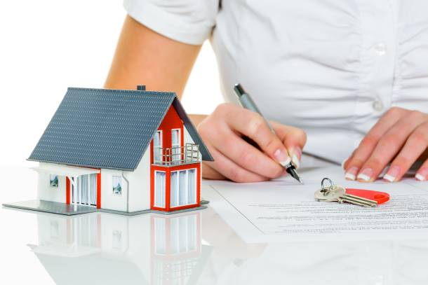 Woman with mortgage contract, model house, and house keys