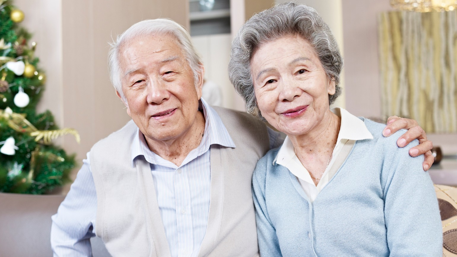 An elderly man with his arm wrapped around his wife at home
