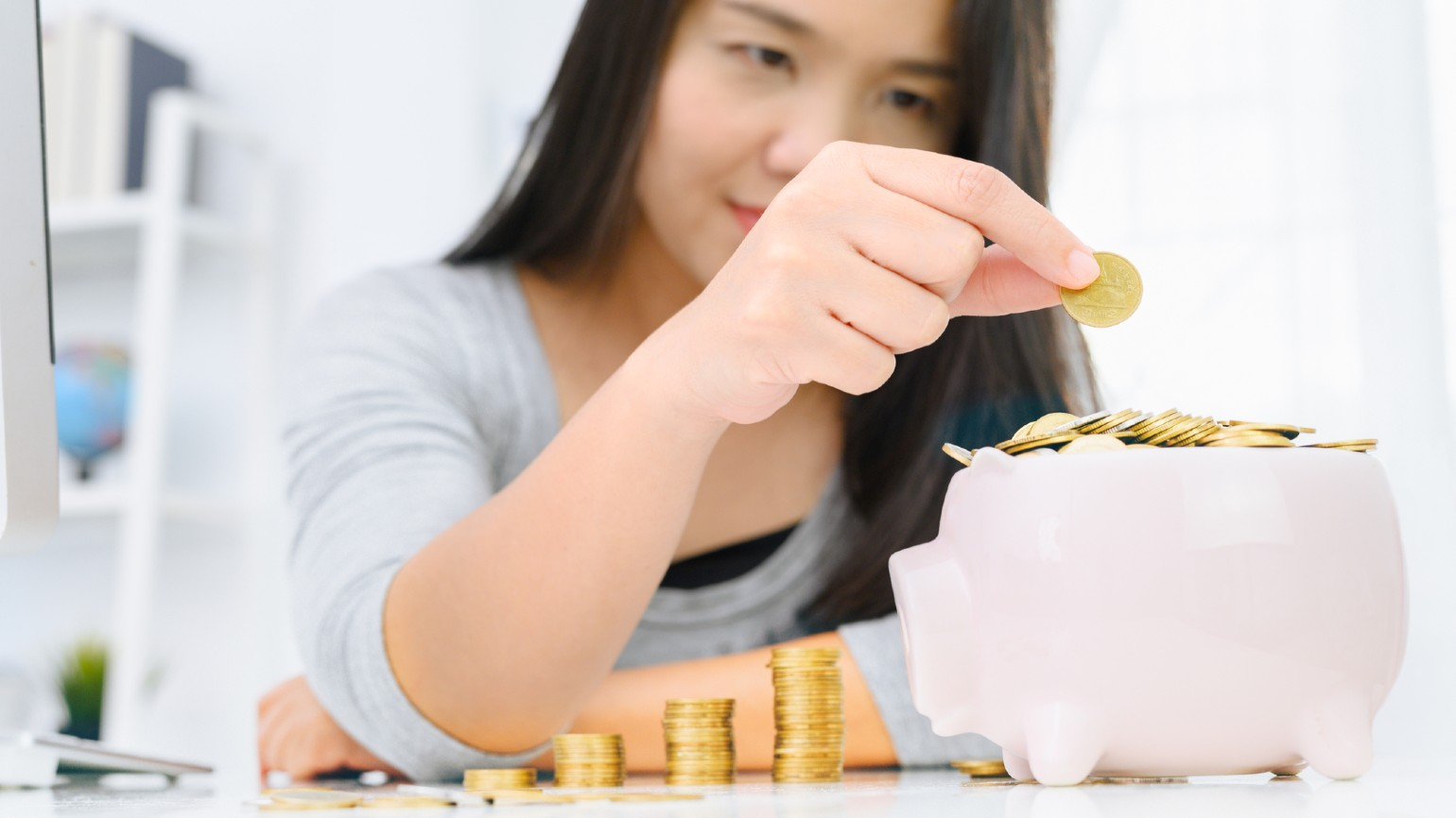 Young woman putting coins into piggy bank