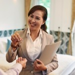 A property agent handing keys to her client