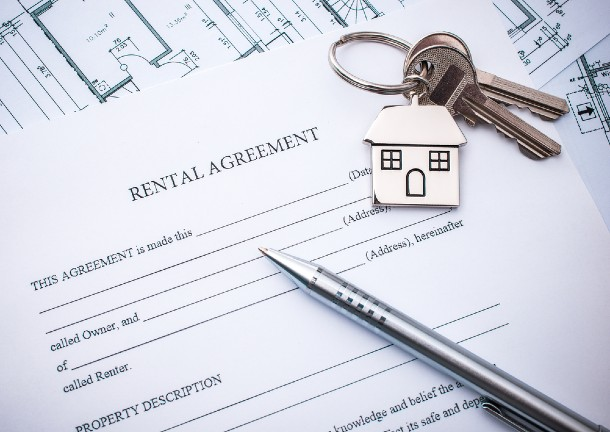 A template of a tenancy agreement, with a pen and a set of house keys resting on top