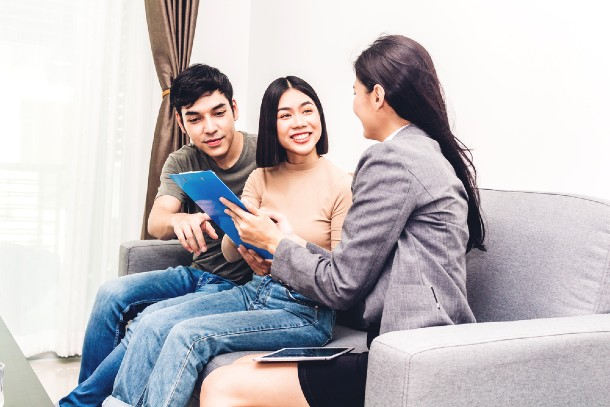 A property agent showing a couple the Letter of Intent document on a clipboard