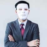 Property agent in a suit and wearing a white mask