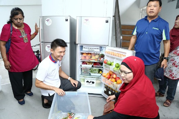 Tampines MP Baey Yam Keng stocking up fresh groceries in the fridge with fellow residents at a Tampines HDB void deck