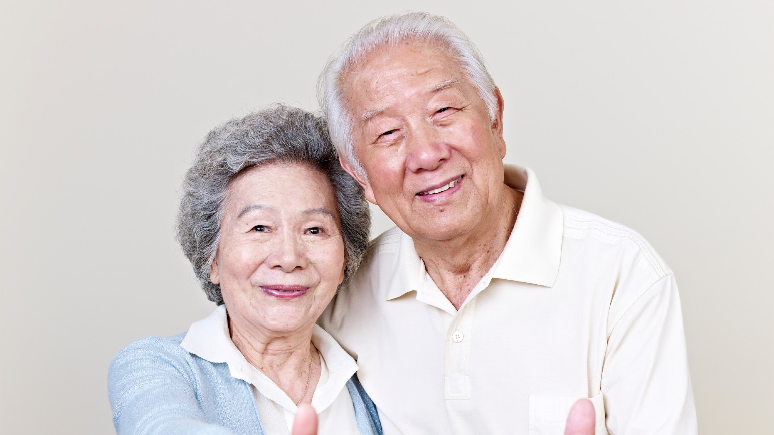 An elderly couple doing a thumbs-up