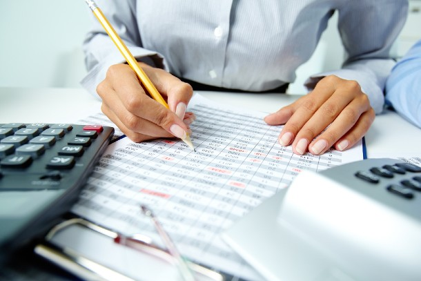 A person working in an accounting business holding a pencil and checking a document, with a calculator by the side