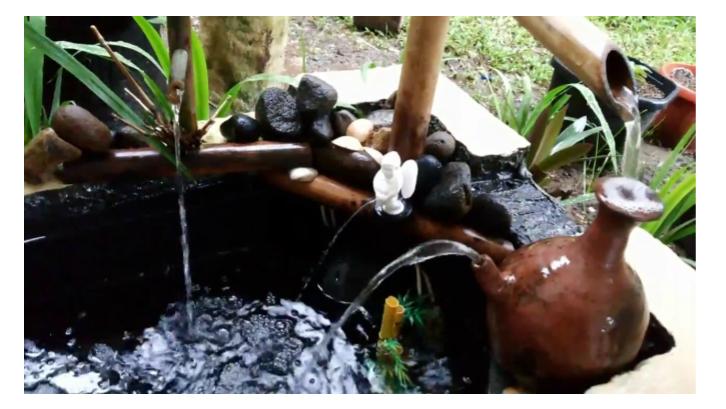 Kendi dari tanah liat dan bambu memberikan nuansa tradisional pada kolam ikan koi. (Sumber: Pinterest.com)