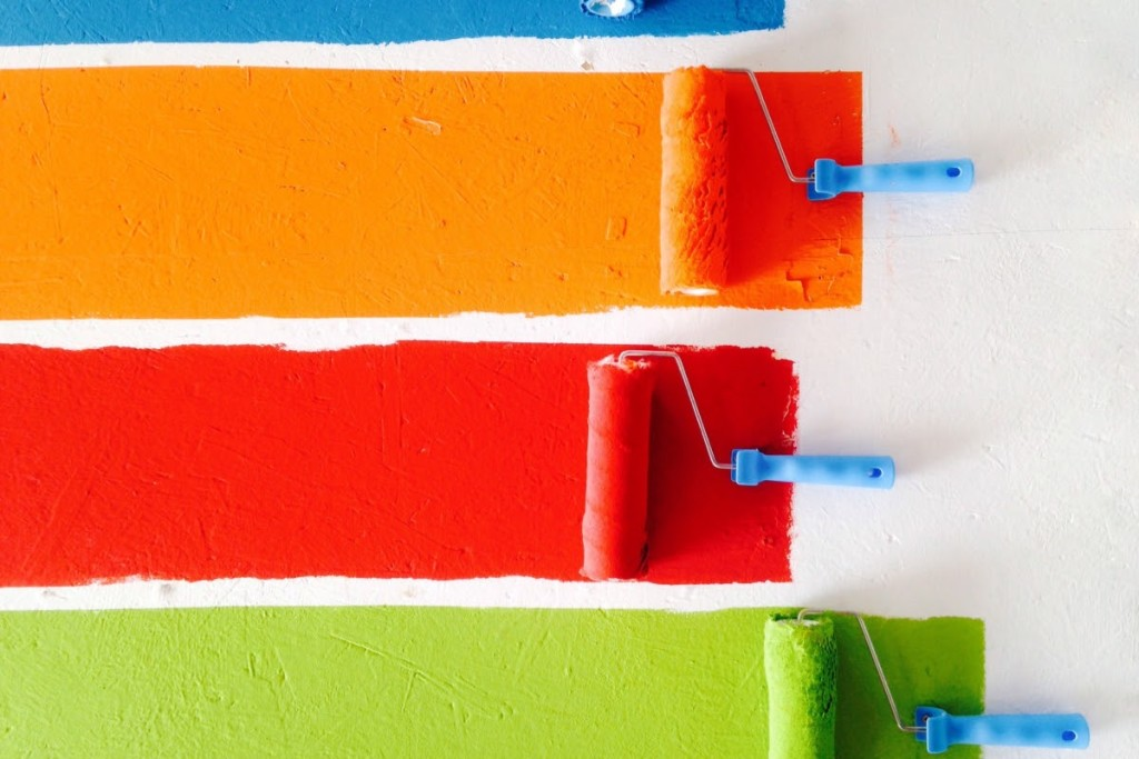 Rollers make green, red, orange and blue paint stripes on a white wall