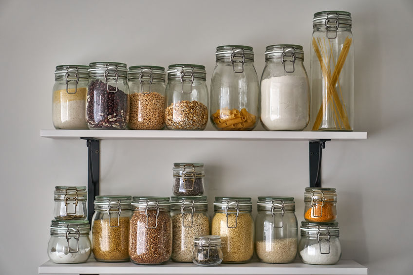 Glass jars with lid food, white shelf. Storage of cereals, pasta on kitchen.