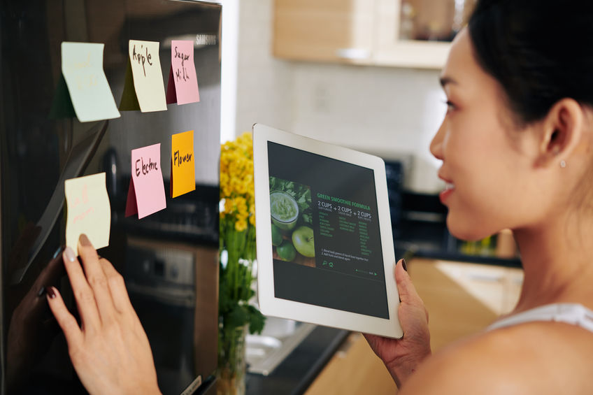 Young woman reading recipe on tablet computer and sticking notes on refrigerator before ordering food delivery
