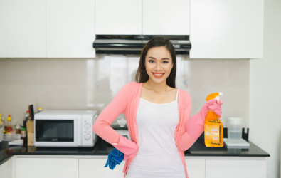 Young asian woman preparing to clean the kitchen. Hand holding detergent spray.