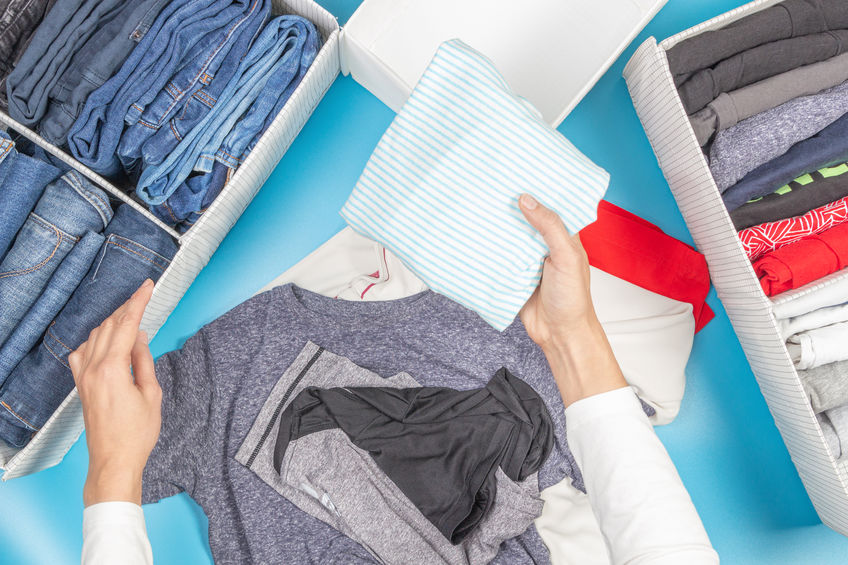 Woman hands folds and puts clothes to baskets. Vertical storage of clothing, tidying up, room cleaning. Marie Kondo style of garments declutter and sorting. Top view